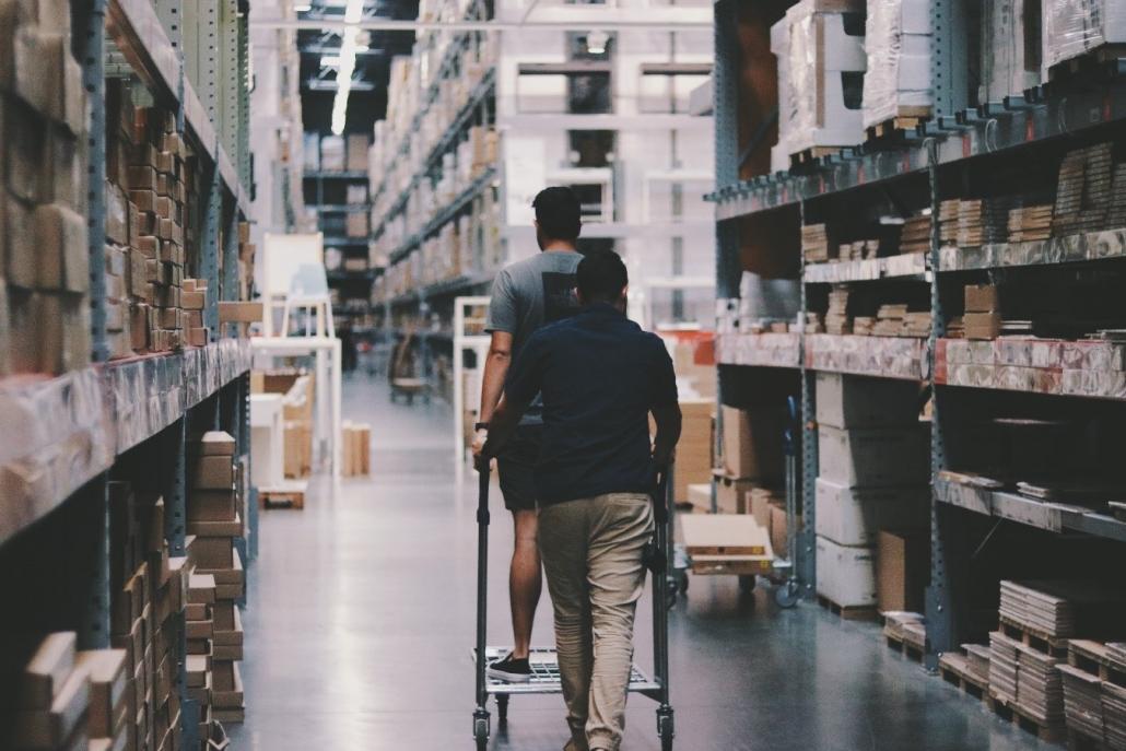Un par de hombres recorriendo un almacén con ayuda de un patín de carga.